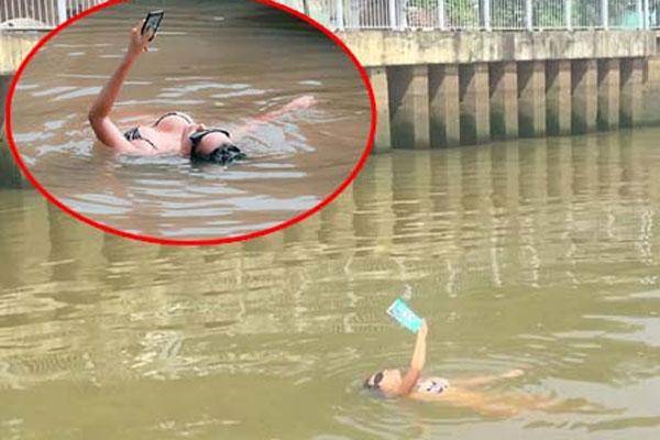 Cô gái mặc bikini nằm ngửa đọc sách để quay clip 'sexy sinh tồn'